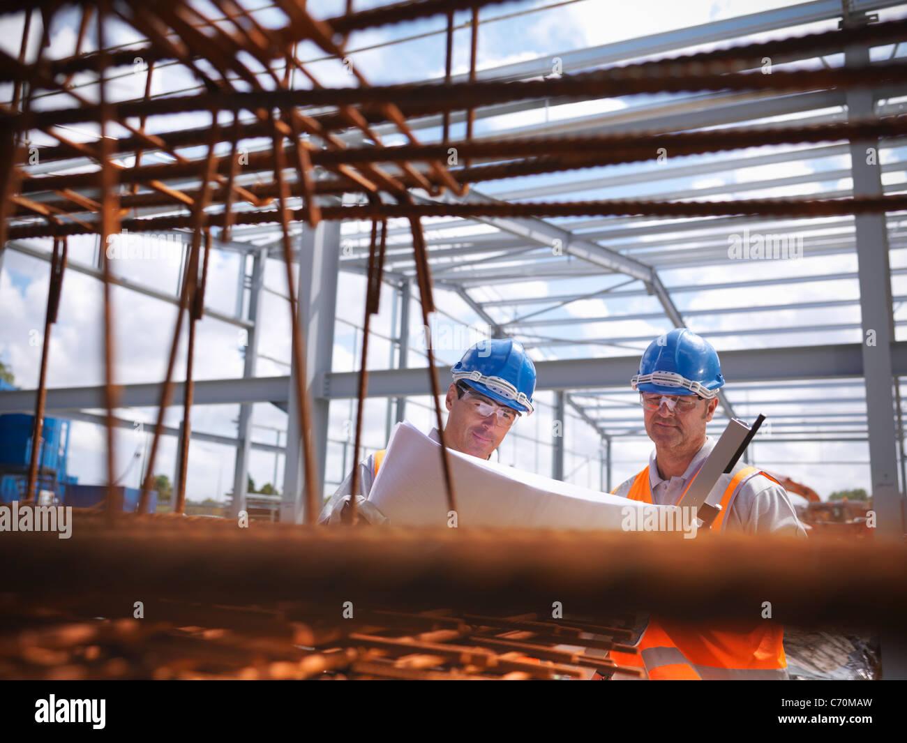 Bauarbeiter, die Baupläne lesen Stockbild