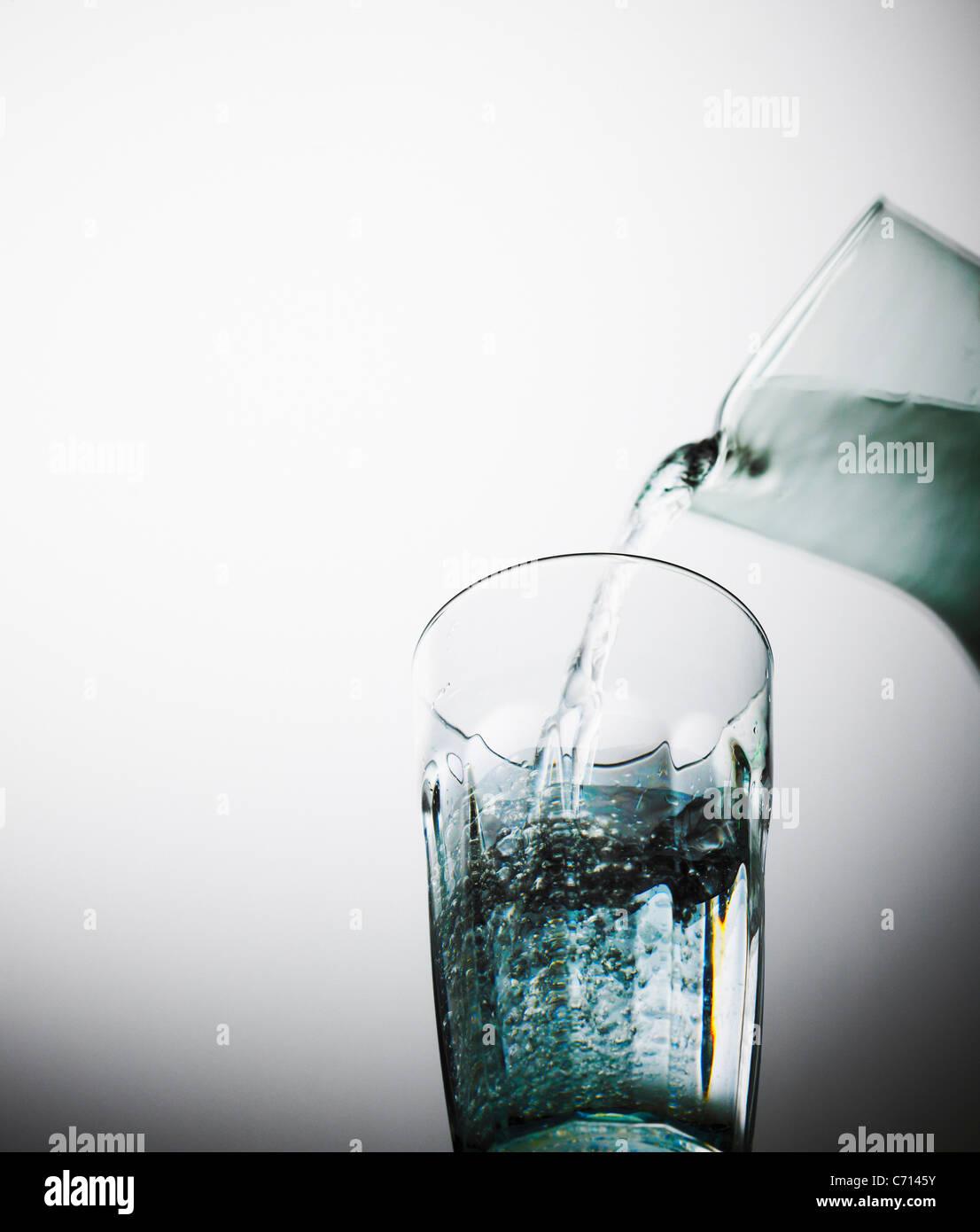Wasser aus einem Krug in ein Glas gegossen wird. Stockbild