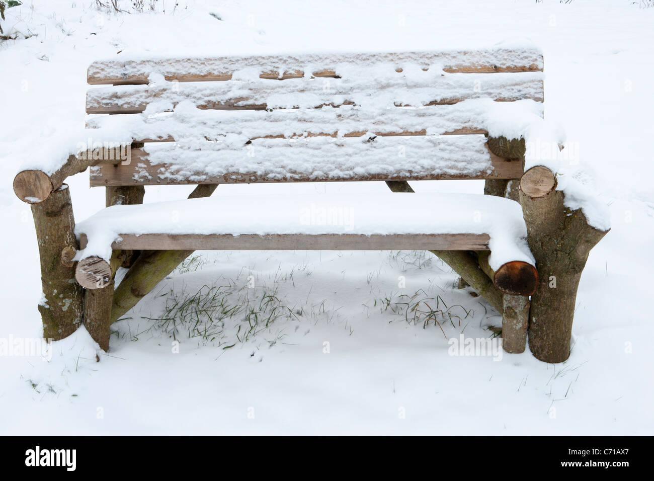Rustikale Gartenbank, hergestellt aus alten Protokollen im Schnee ...