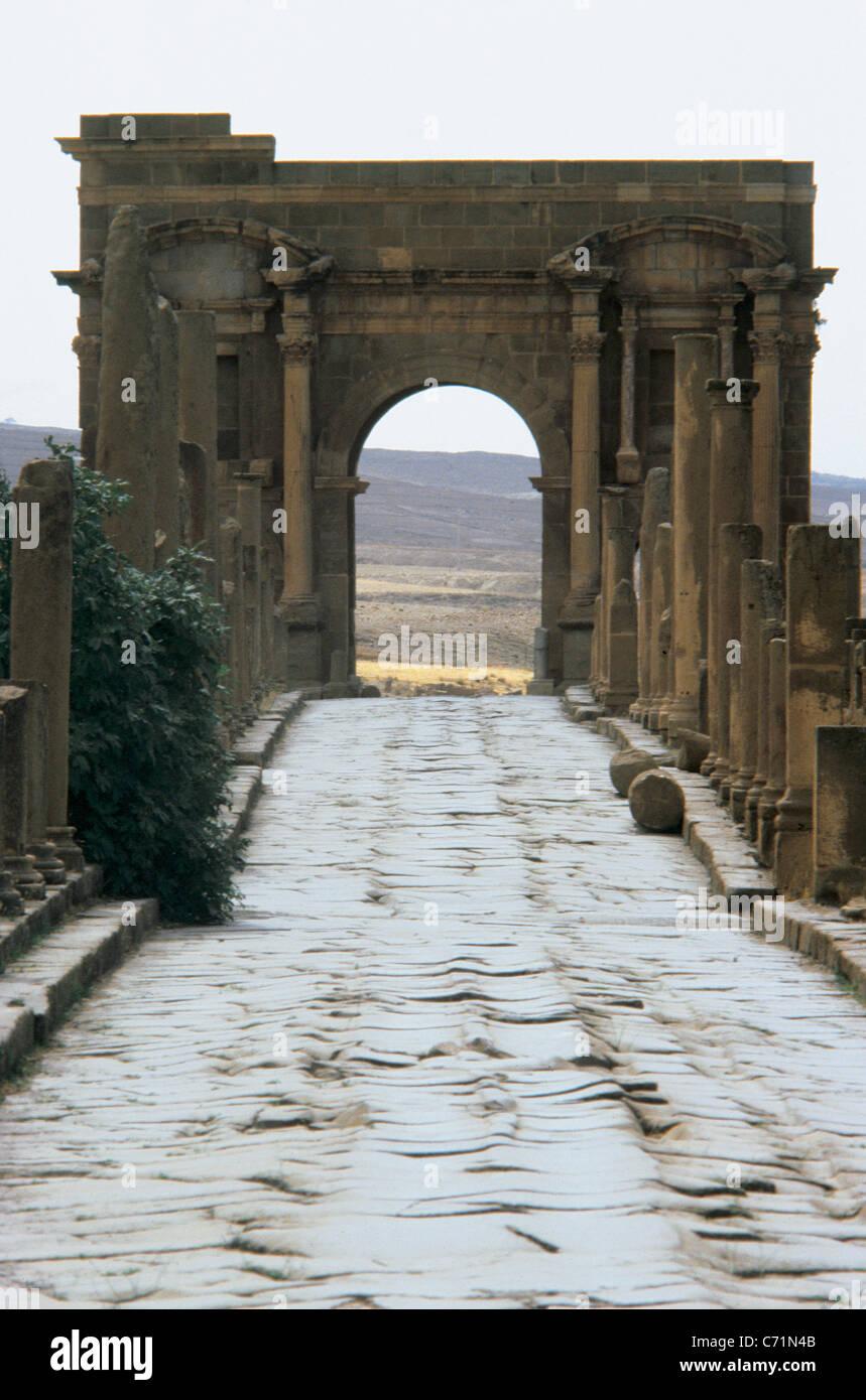 Römische Kunst. Algerien. Timgad. Römische Causeway und Trajan Bogen im Hintergrund. Stockbild
