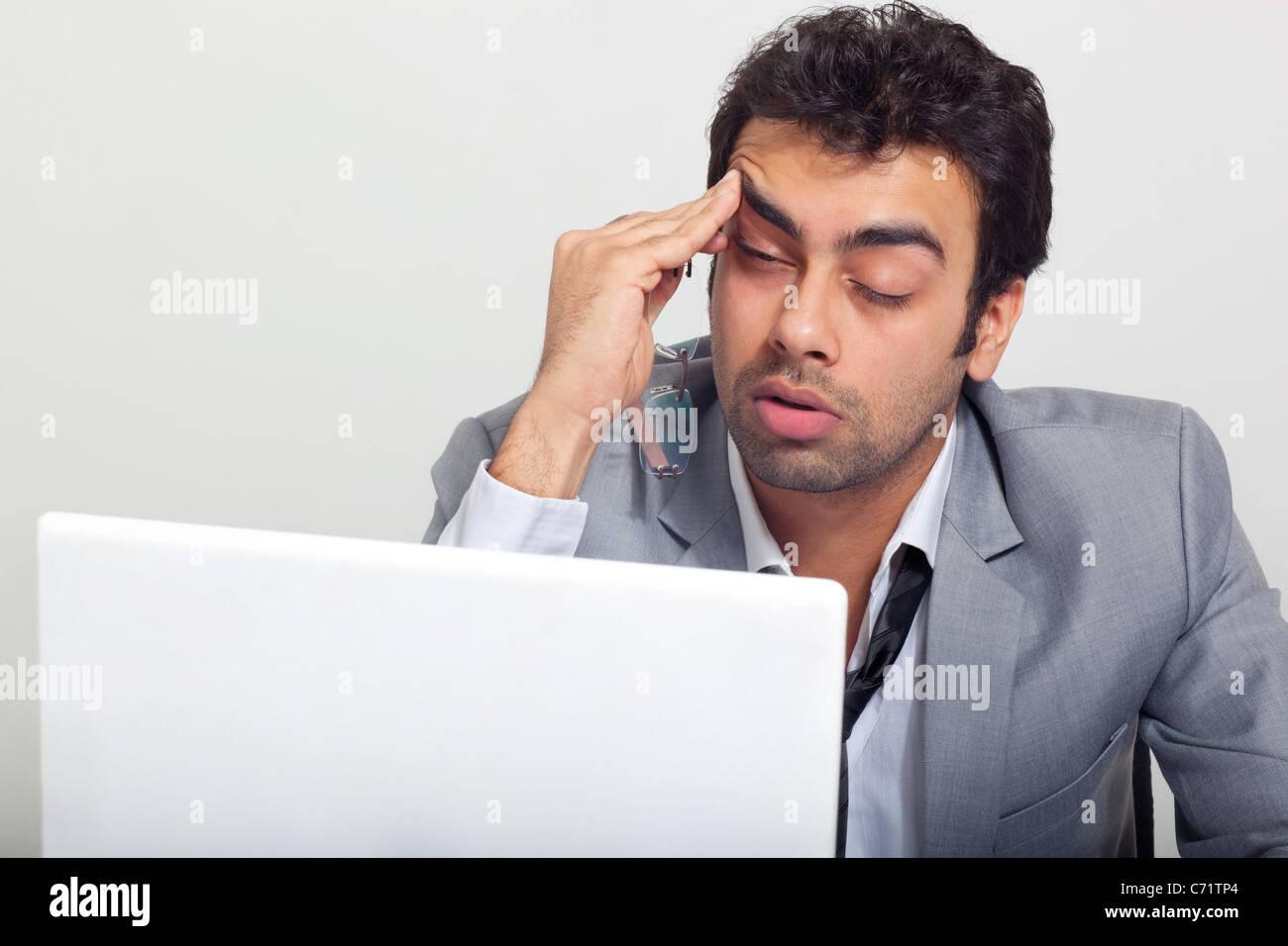 Geschäftsmann am Arbeitsplatz schläfrig fühlen Stockbild