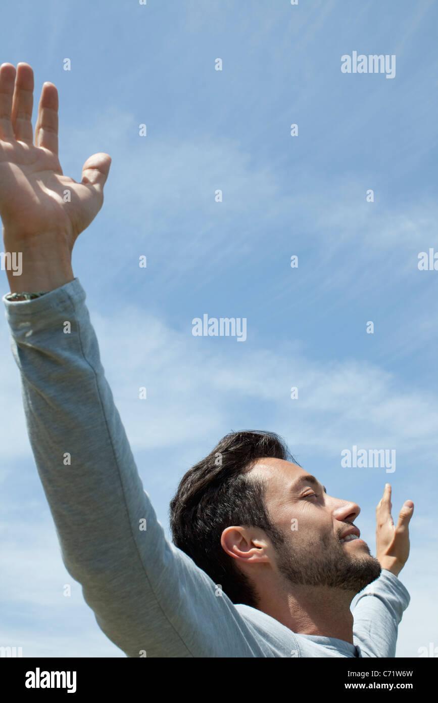 Mann im Freien mit ausgestreckten Armen und Augen geschlossen Stockbild