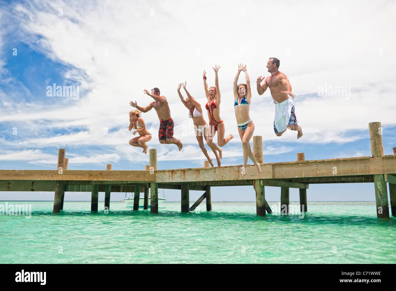 Eine Gruppe von Freunden springt aus Holz Dock in der kühlen Karibik Stockfoto