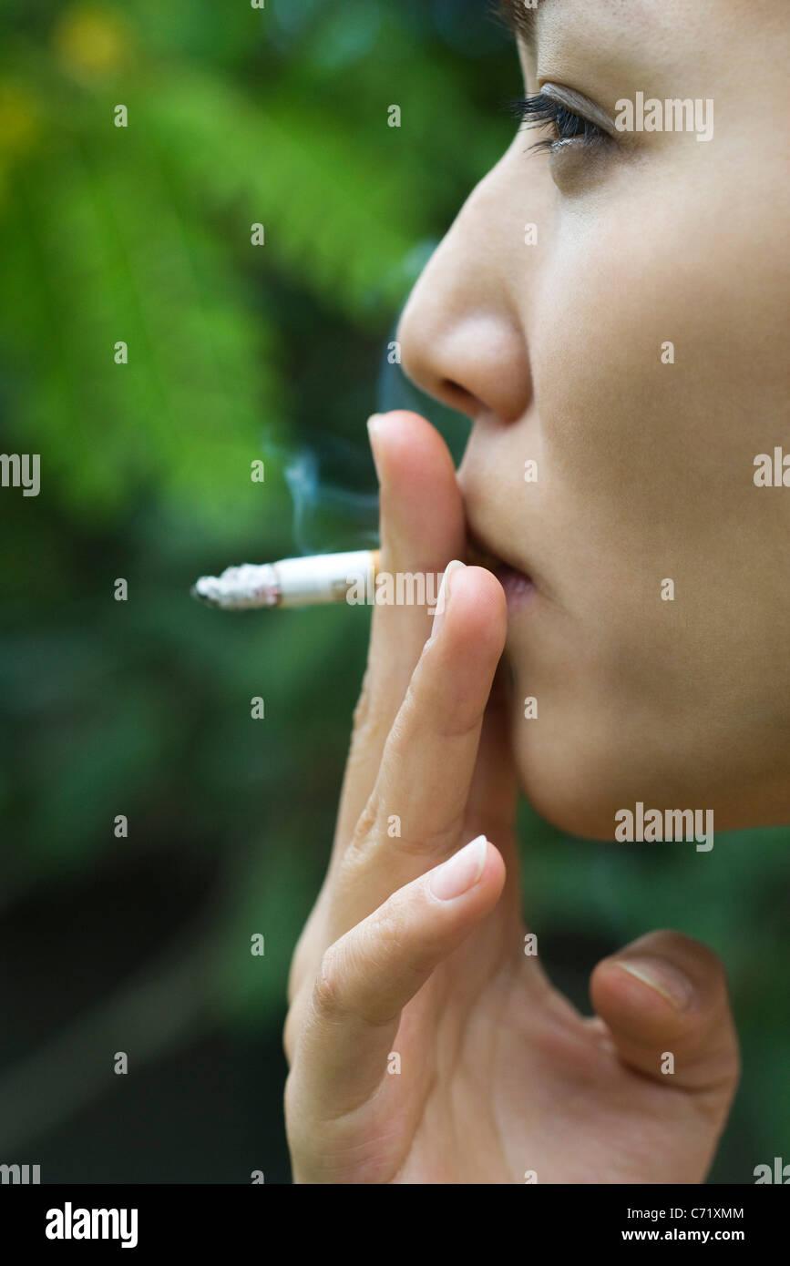 Junge Frau, die das Rauchen im Freien, Seitenansicht Stockbild