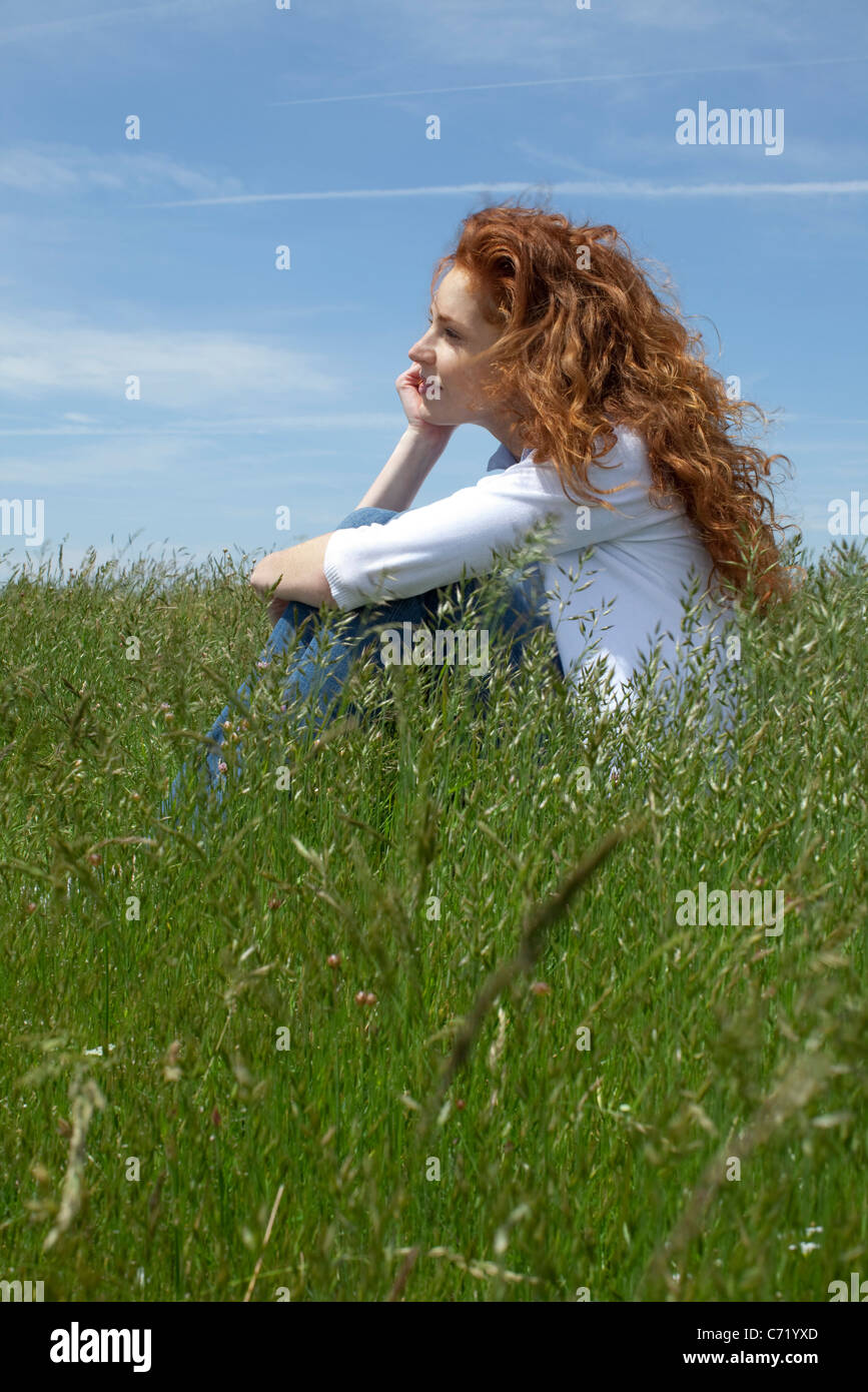 Frau Tagträumen auf Wiese Stockfoto