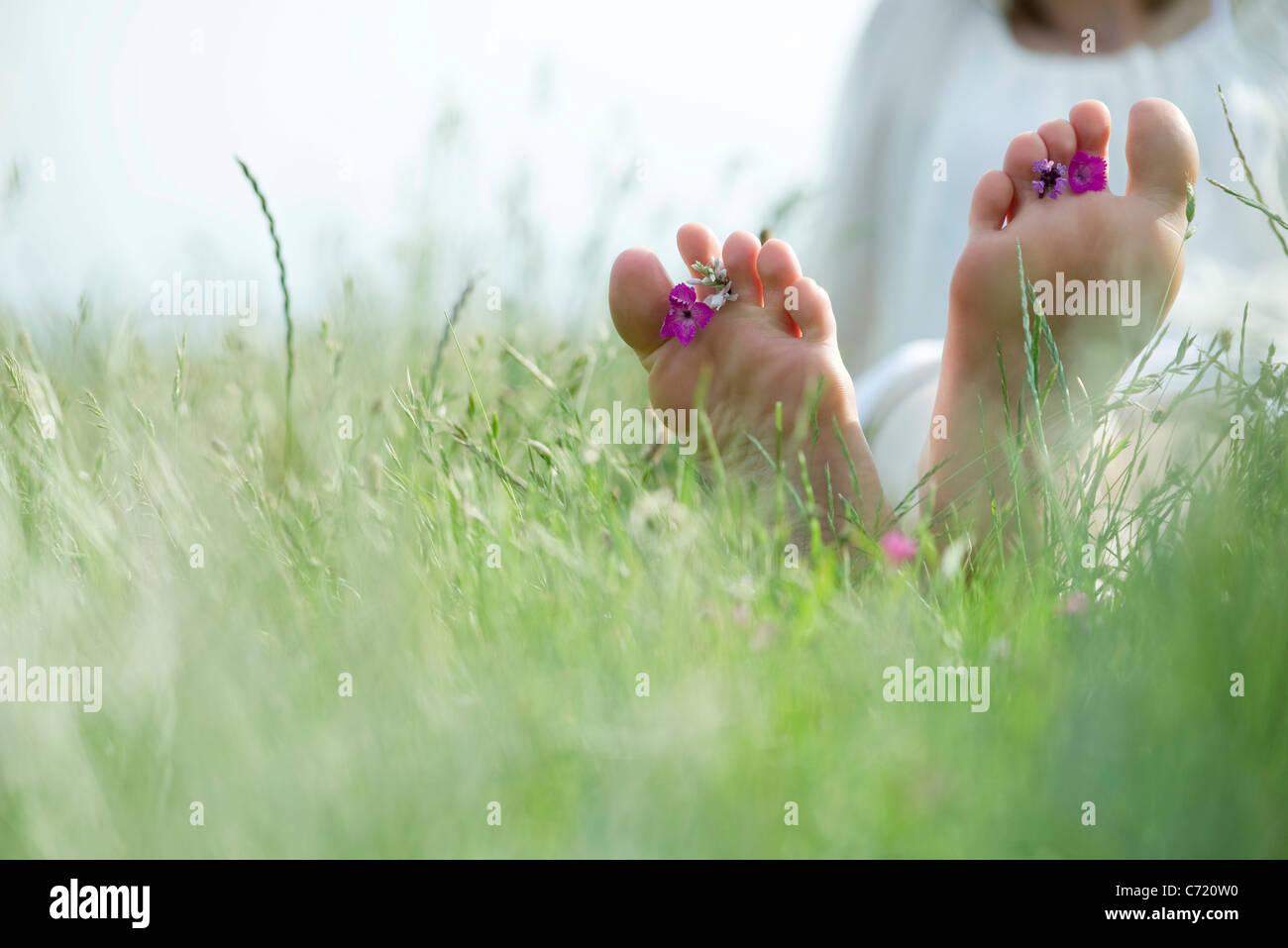 Barfuß junge Frau sitzt auf Wiese mit Wildblumen zwischen Zehen, beschnitten Stockfoto