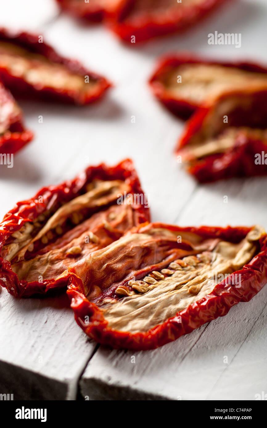 Getrocknete Tomaten auf weißem Holz Stockbild