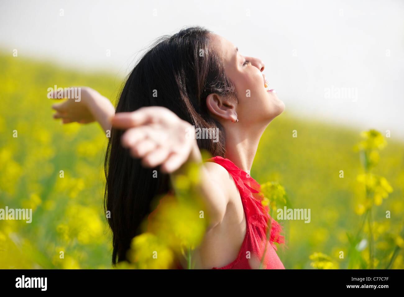 Junge Frau amüsiert sich in einem Feld Stockbild