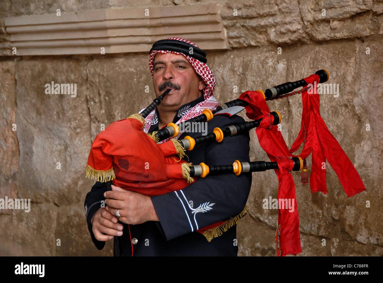 Jordanische Dudelsackspieler mit einem roten Dudelsack gegen eine Wand. Stockfoto