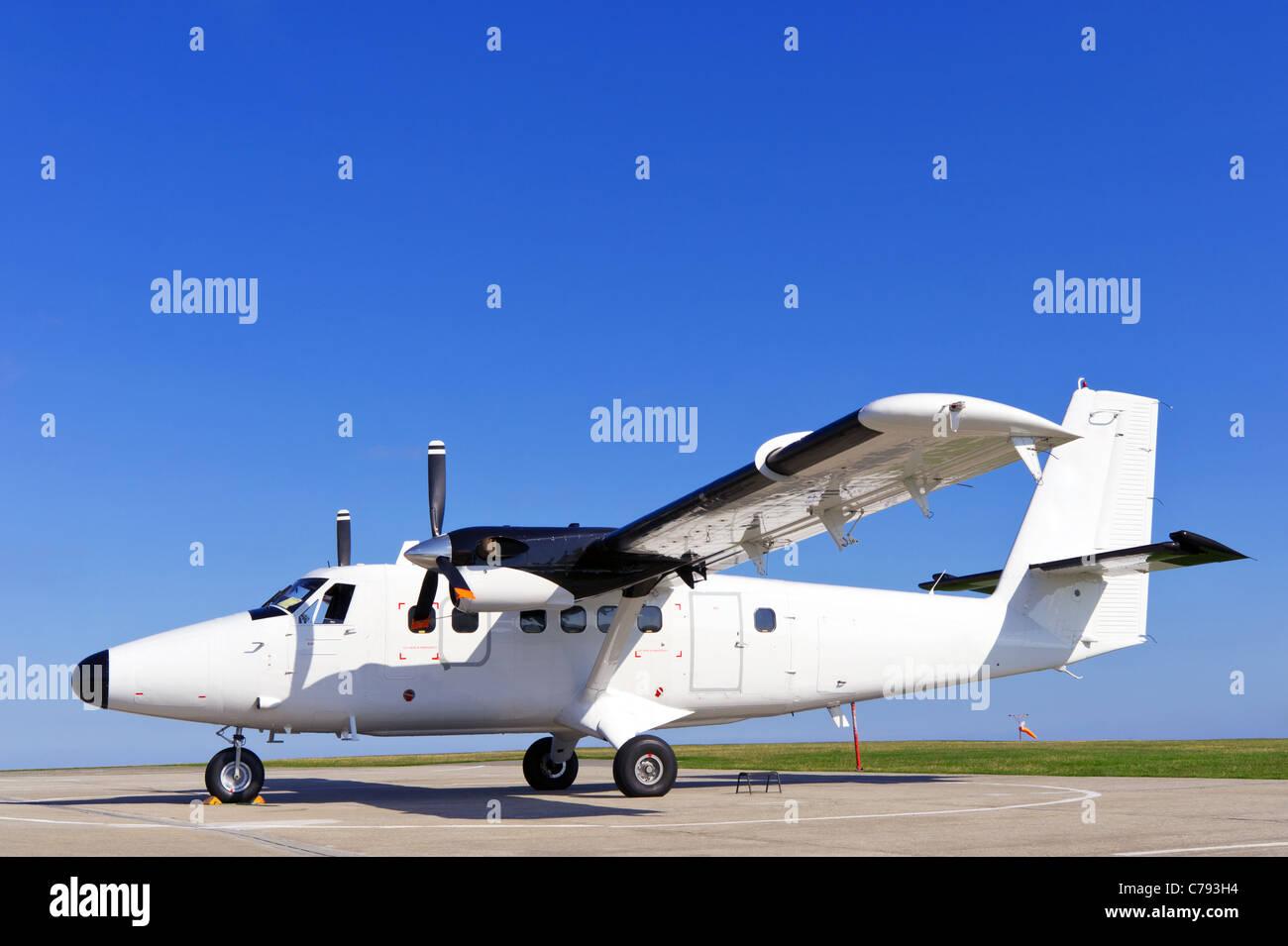 Foto der eine Zwilling-Propellermaschine stationär auf der Piste an einem sonnigen Tag mit klaren blauen Himmel. Stockbild