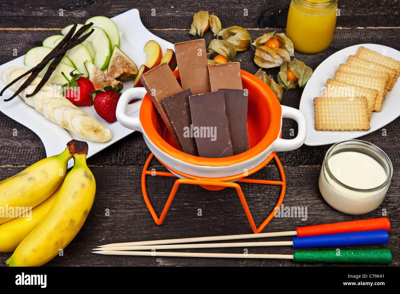 frische Zutaten für ein typisches Schweizer Schokoladen-Fondue mit Obst und Gebäck Stockbild