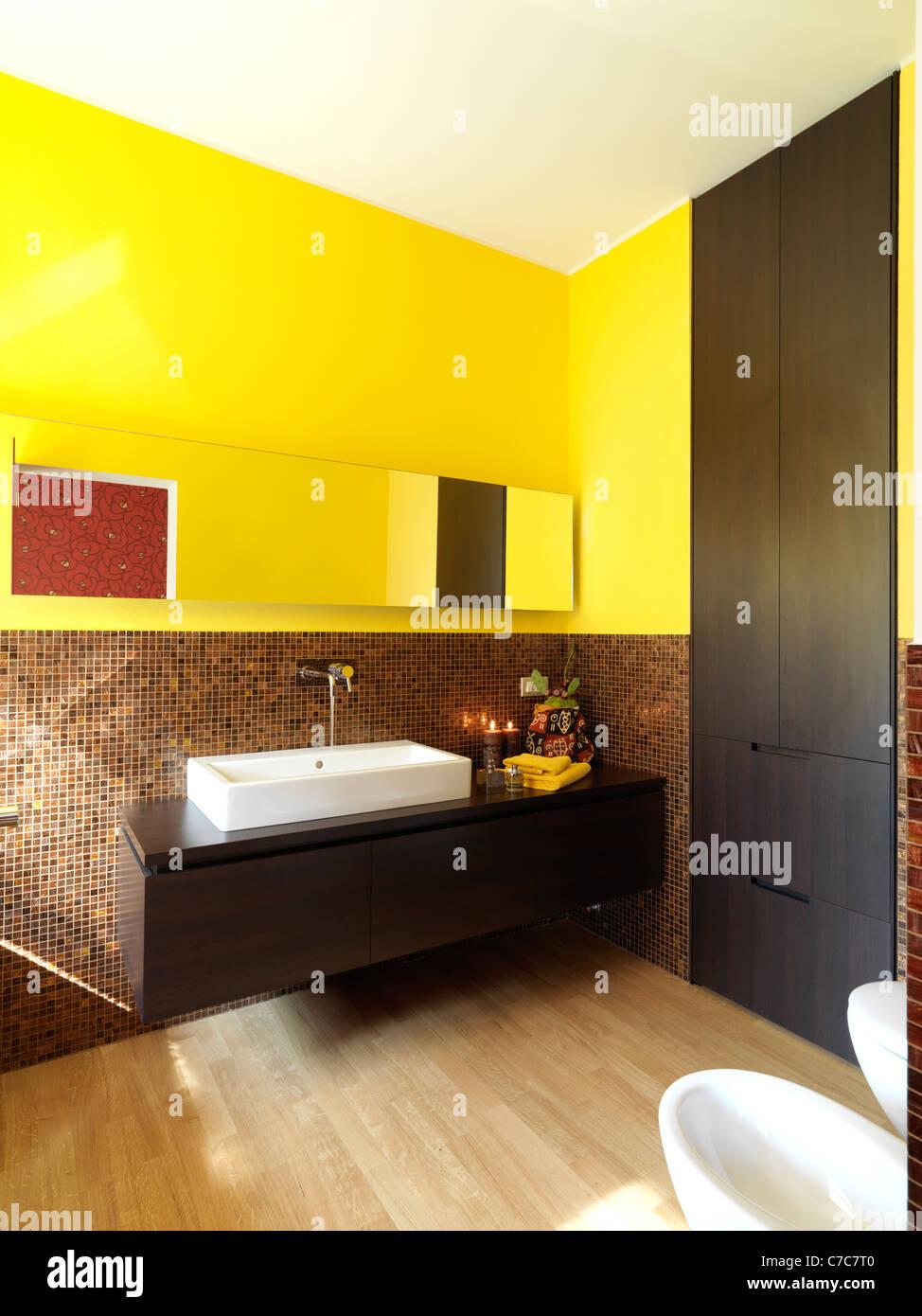 Modernes Badezimmer Mit Gelben Wand Und Fussboden Aus Holz Stockfoto