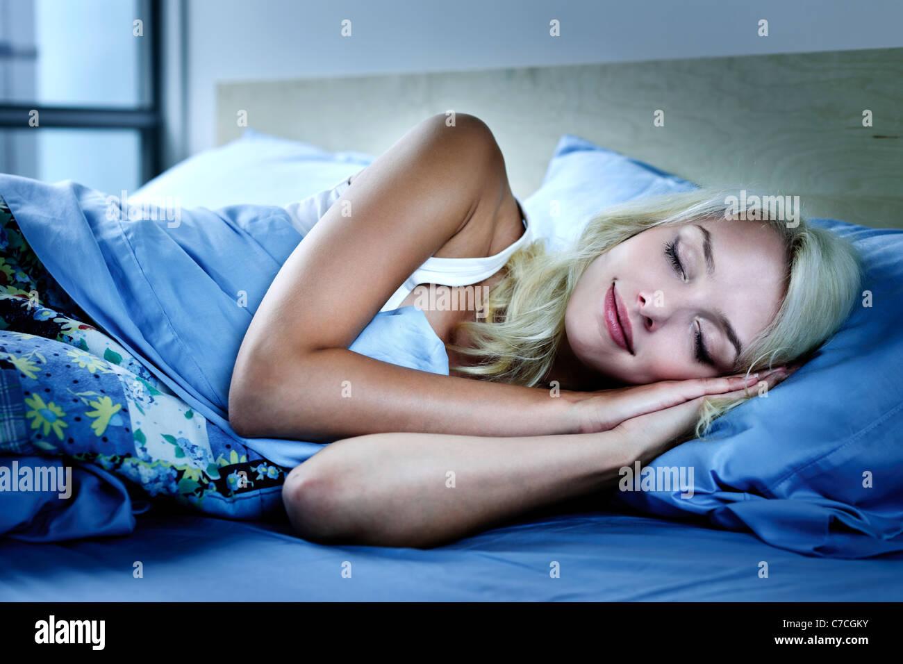 Junge Frau schlafen friedlich in der Nacht im Bett Stockbild
