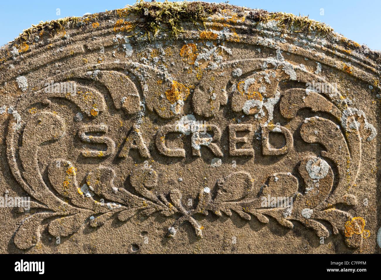 Sacred - auf einem Grabstein in einem Cotswold-Kirchhof Stockbild