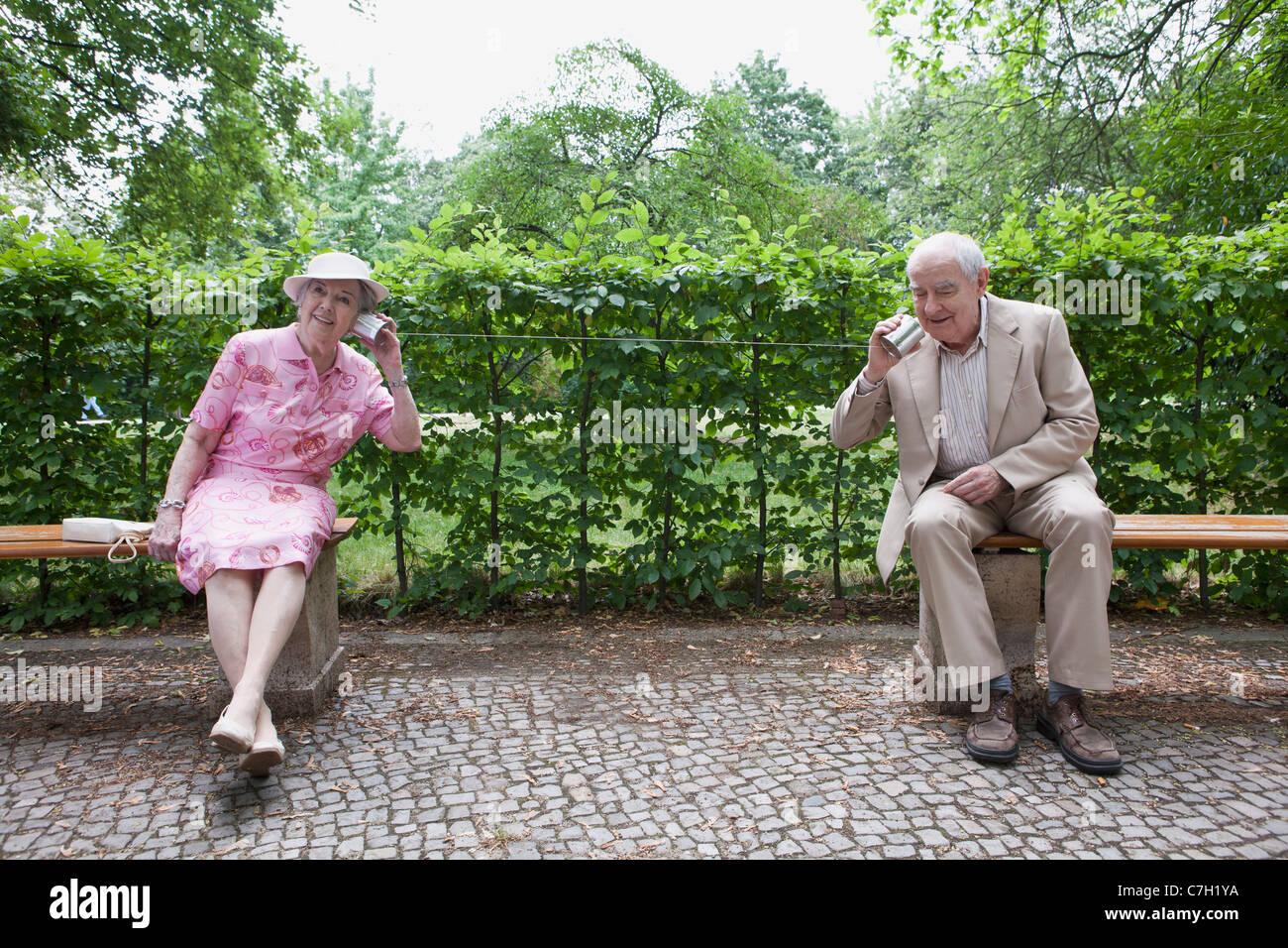 Ältere Mann und Frau sprechen miteinander, auf Blechdose Handys im park Stockfoto