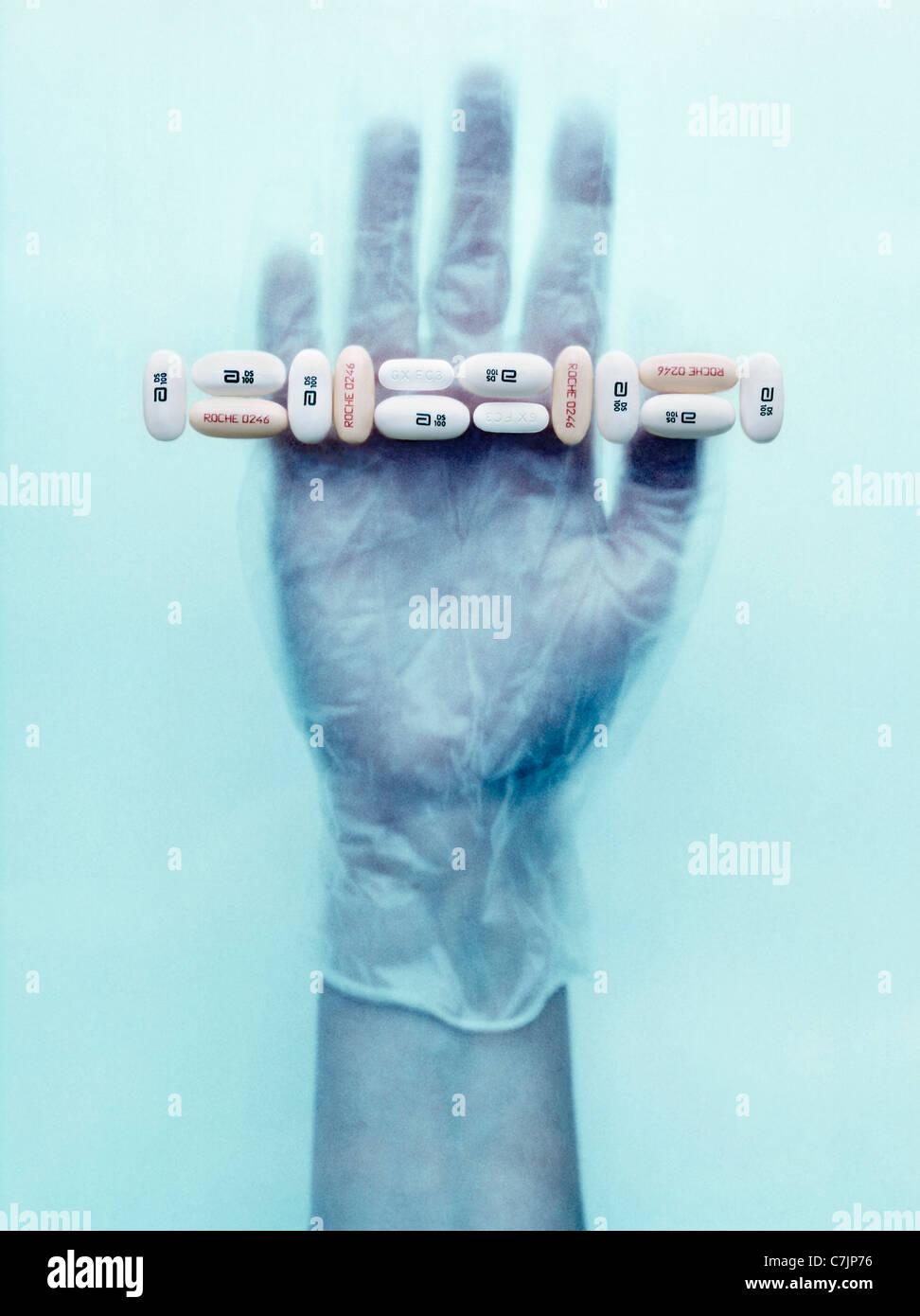 Behandschuhte Hand, die Pillen Stockfoto