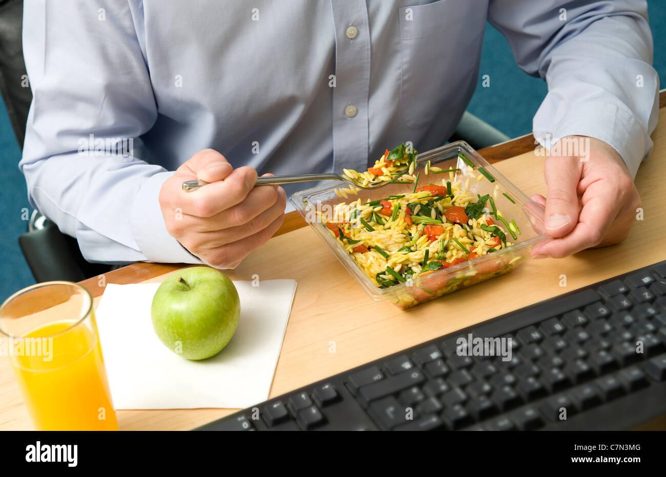 männlicher Büroangestellter Essen Arbeitsessen Stockbild