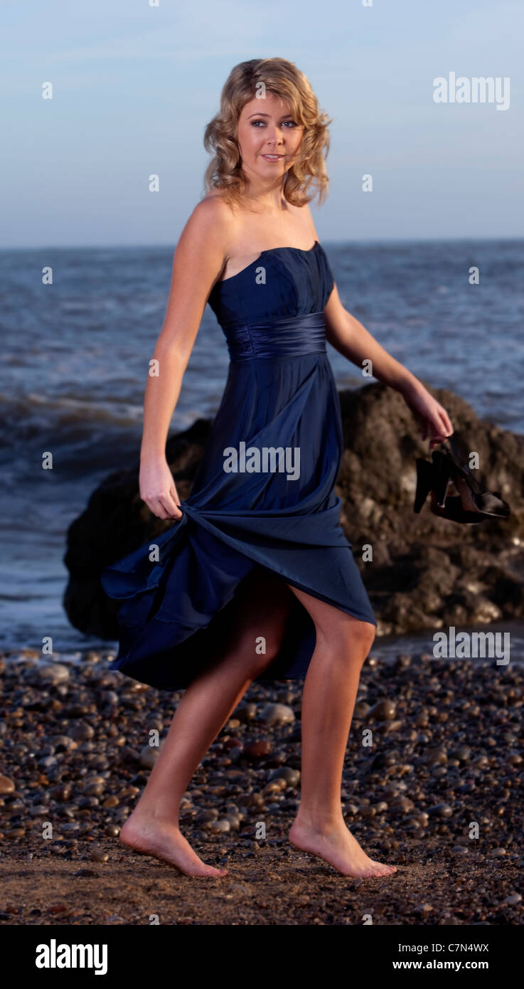 Eine hübsche junge Frau trägt eine blaue Partykleid barfuß am Strand ...