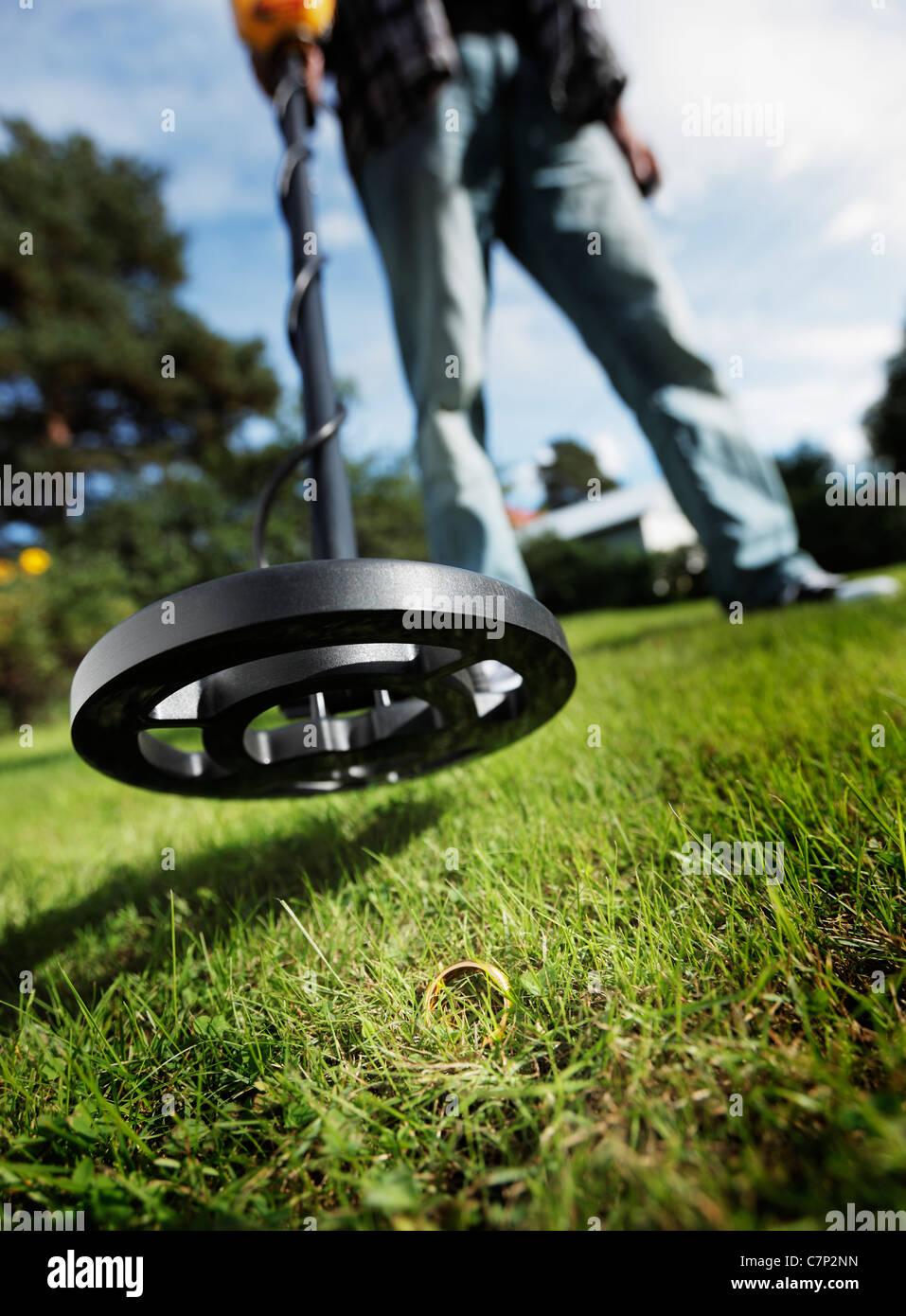 Mann finden, einen goldenen Ring im Rasen mit einem Metalldetektor. Stockbild