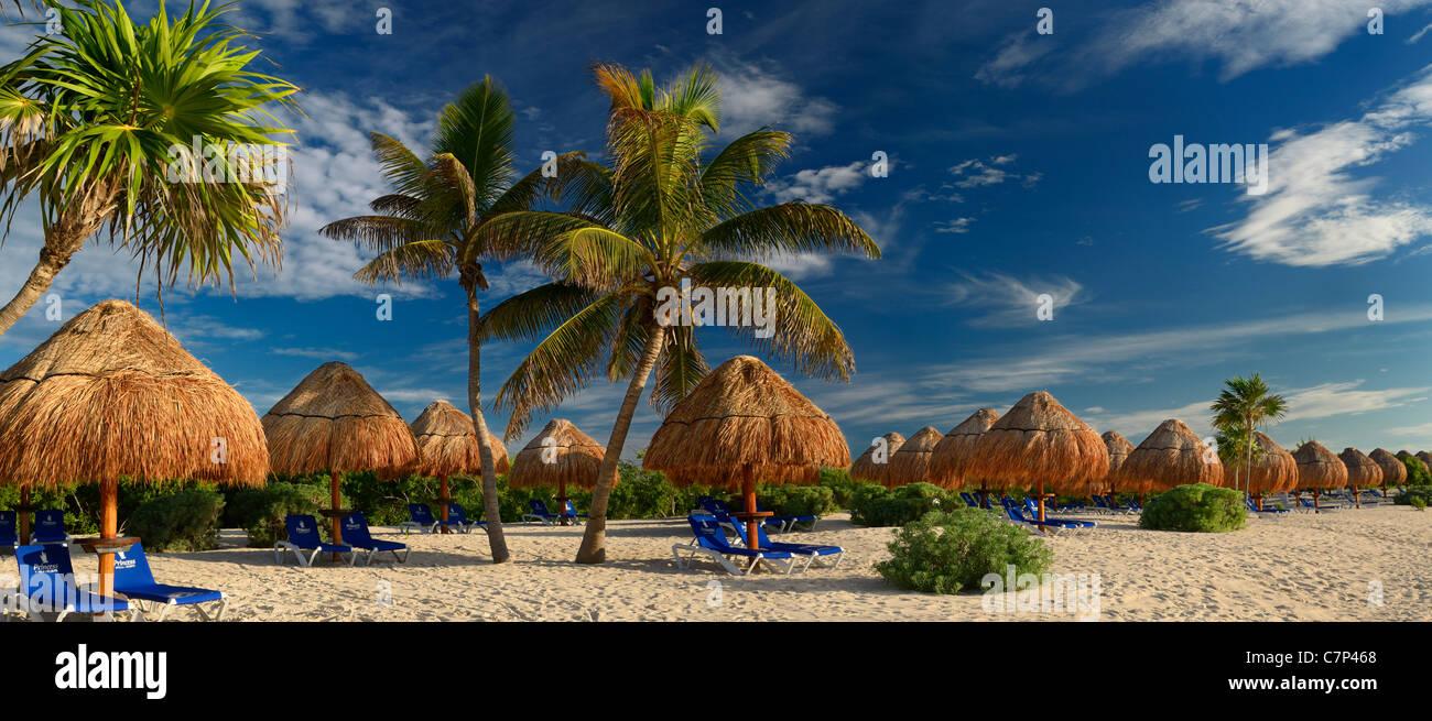 Panorama von leeren Riviera Maya Beach mit strohgedeckten Sonnenschirmen und Kokospalmen Mexiko Stockbild