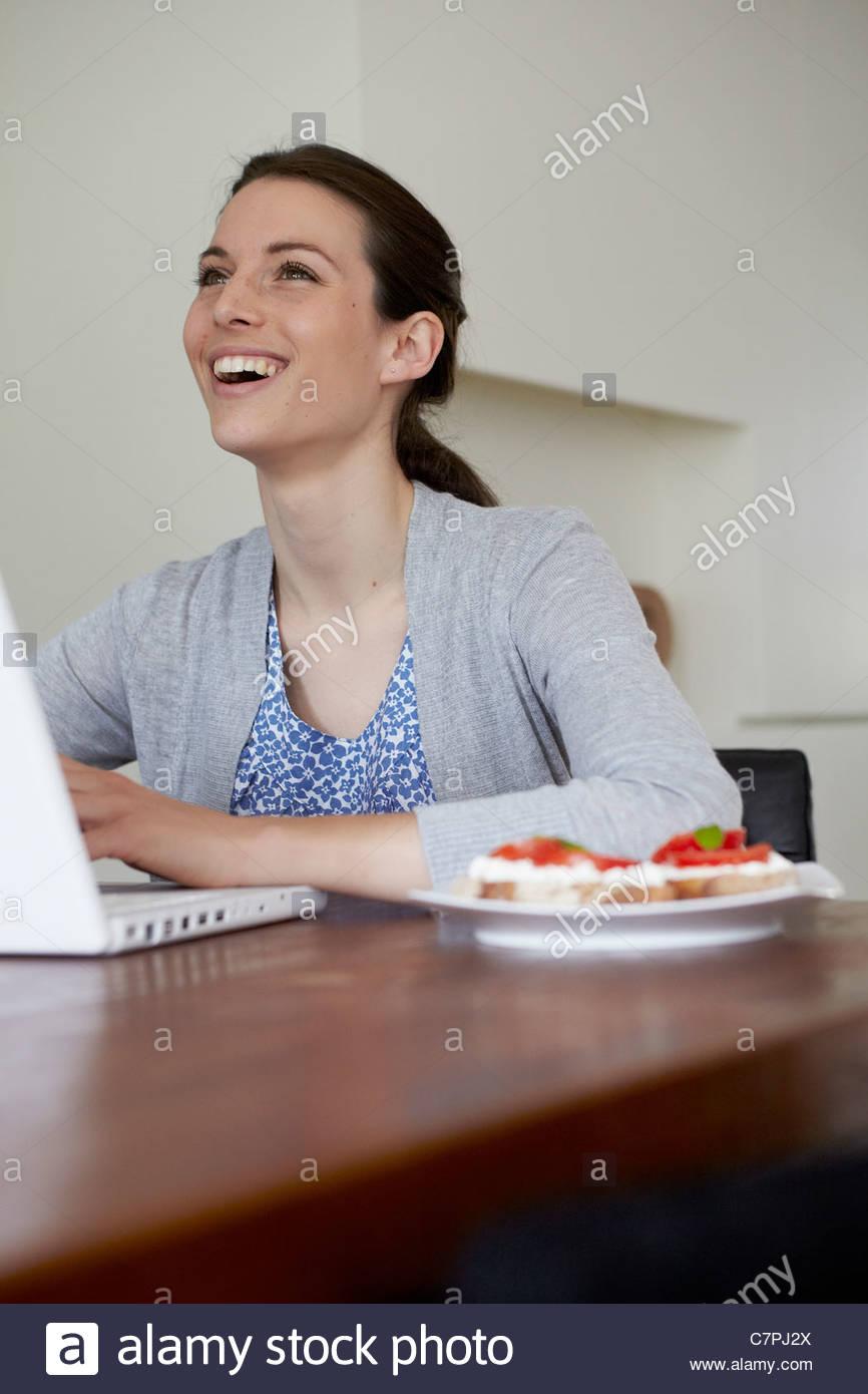 Frau mit Laptop mit Teller mit Essen Stockbild