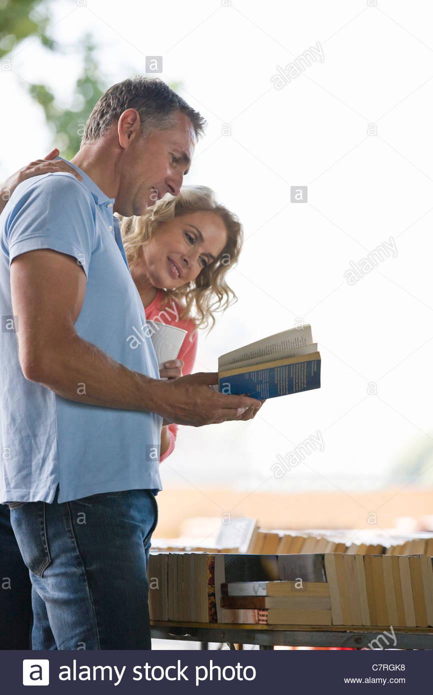 Ein paar mittleren Alters, die Bücher in einem Buch stand anschauen Stockbild