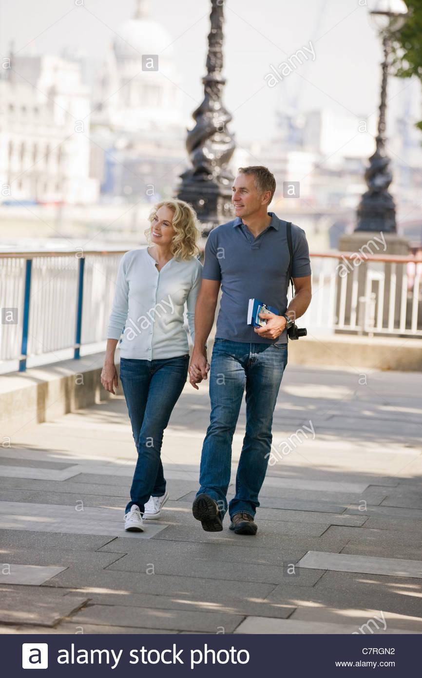 Ein paar mittleren Alters, die hand in hand gehen, neben dem Fluss Themse Stockbild