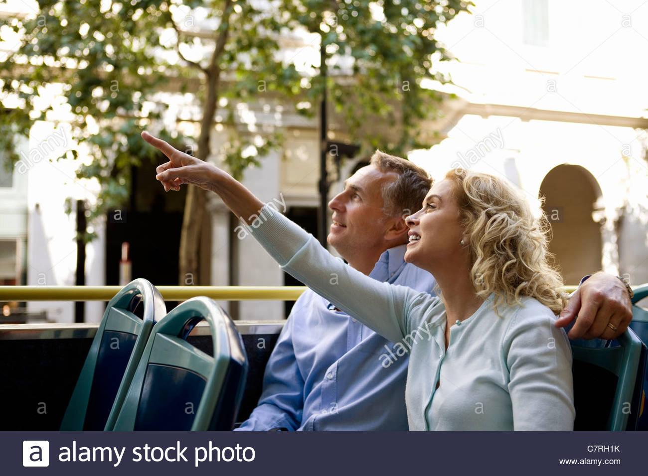 Ein paar mittleren Alters sitzen auf einem Sightseeing-Bus, bewundern Sie die Aussicht Stockbild