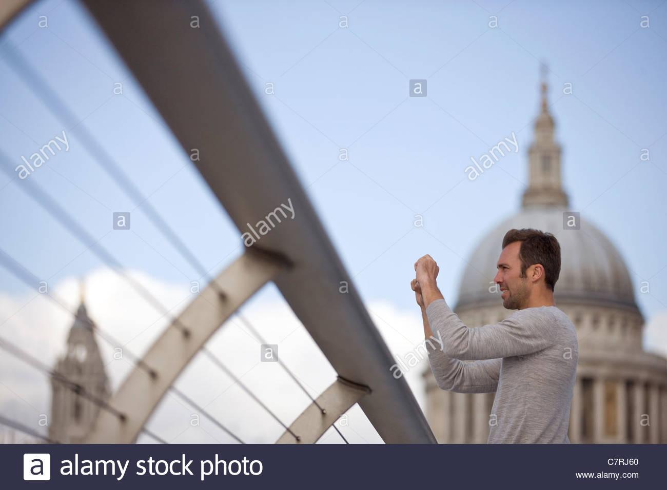 Ein Mid-Adult-Mann steht auf die Millennium Bridge, ein Foto Stockbild