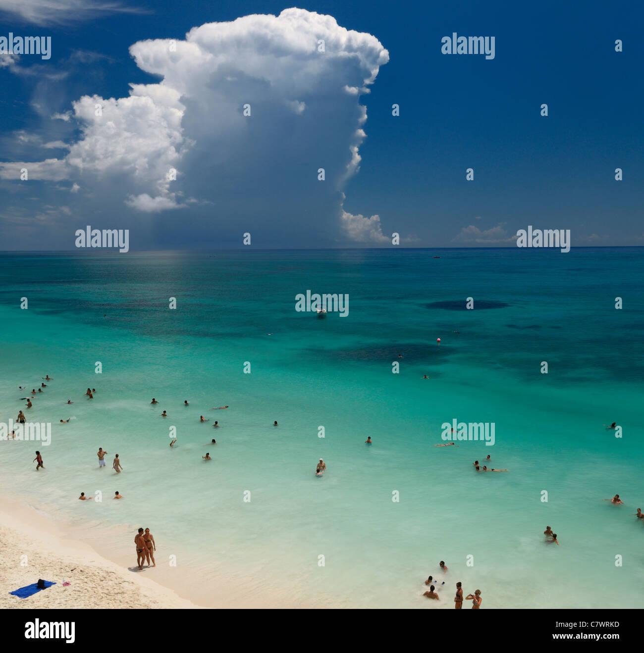 Menge der Badegäste am Strand in Tulum Mexiko im türkisblauen Meer mit Storm cloud Riviera Maya Halbinsel Stockbild