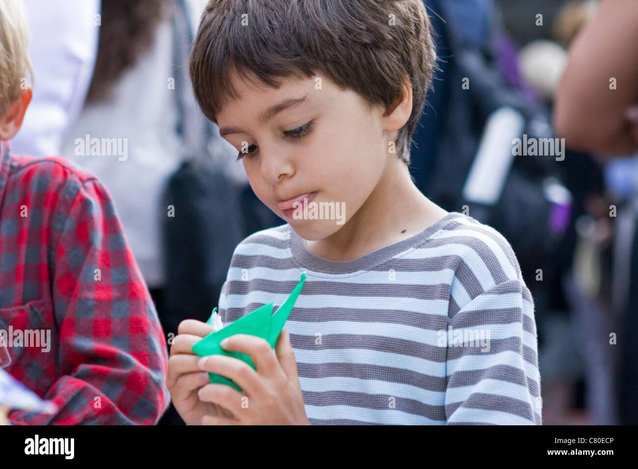 Ein kleiner Junge arbeitet an seinem Origami Papier Kran. Stockbild