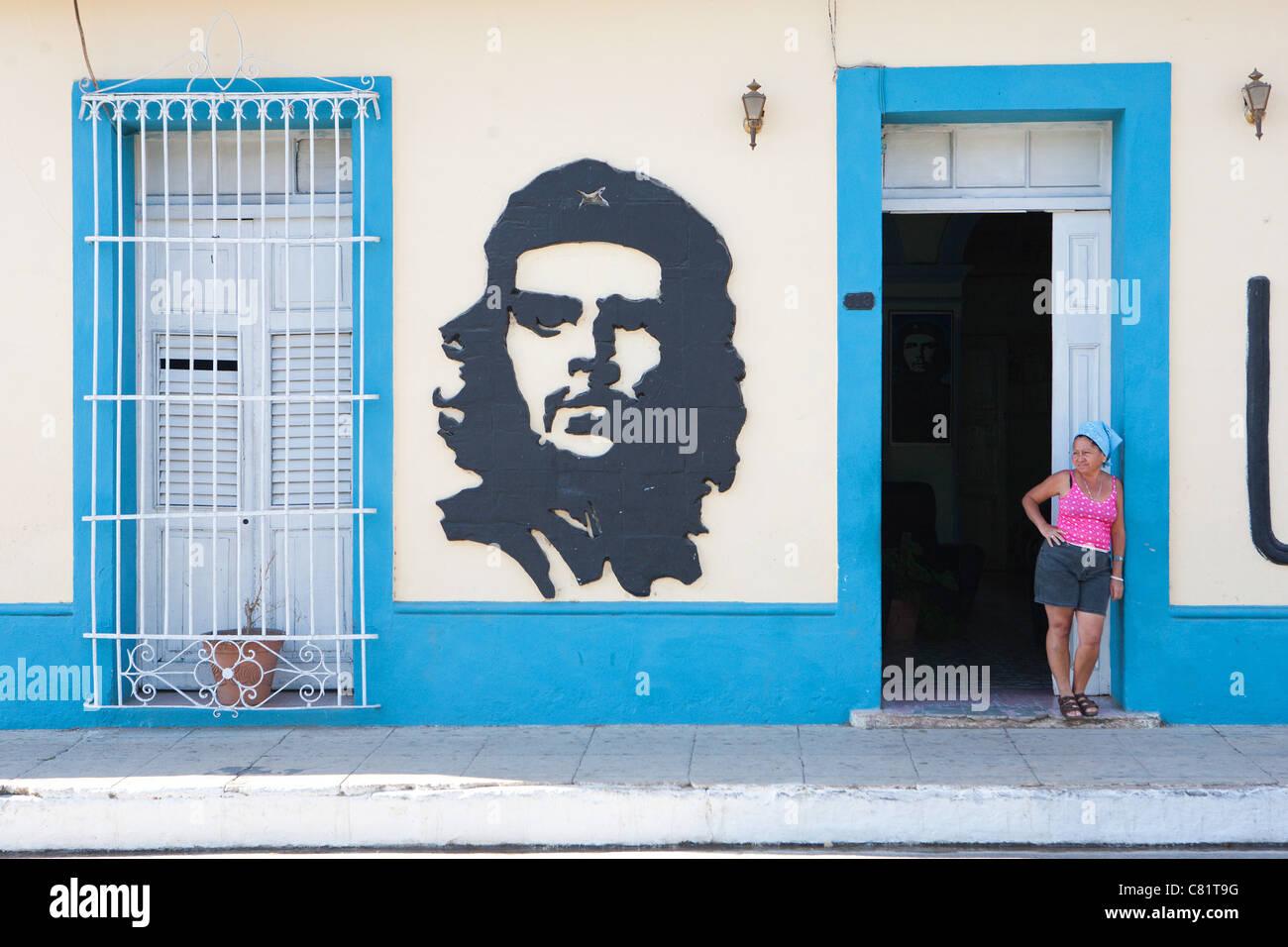 TRINIDAD: KUBANISCHE FRAU WARTEN DURCH REVOLUTIONÄRE STREETART VON CHE GUEVARA Stockbild