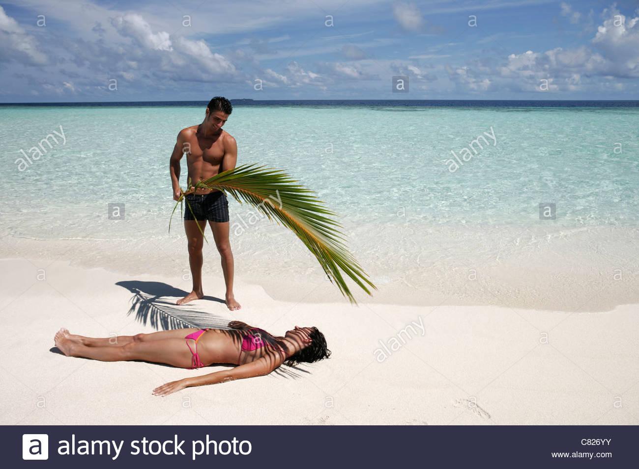 malediven paar am strand mann die frau vor der sonne mit einem palmblatt abschirmung. Black Bedroom Furniture Sets. Home Design Ideas