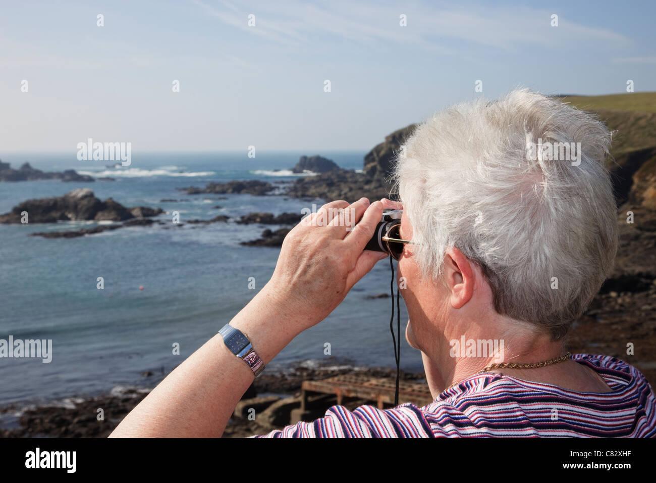 Ältere Frau Rentner durch ein Fernglas mit Meerblick auf die Küste am südlichsten Punkt auf dem Festland Großbritannien.Stockfoto