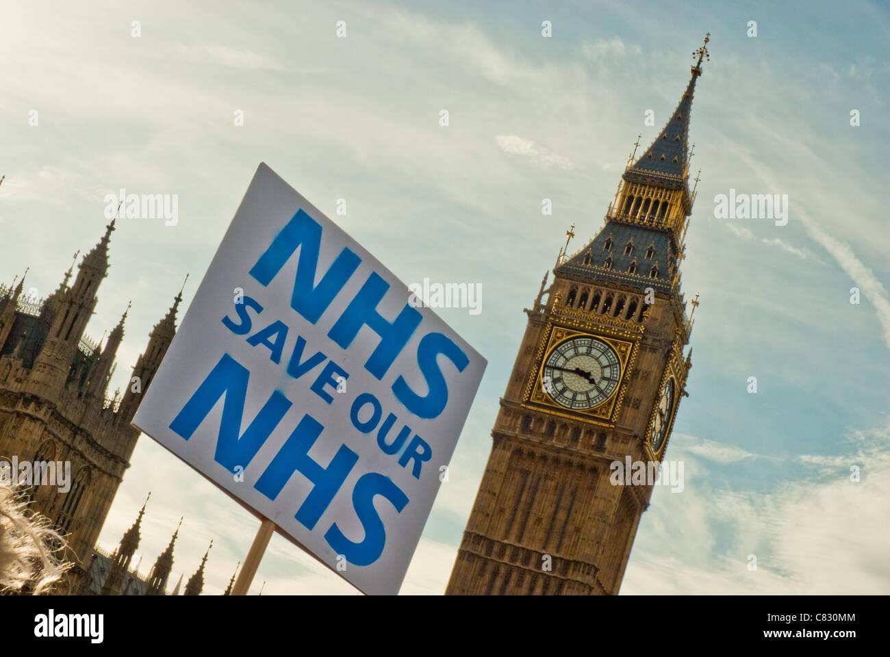 Einzelne Plakat 'NHS SPEICHERN UNSERE NHS' gegen Big Ben sowohl auf jaunty Winkel. Stockbild