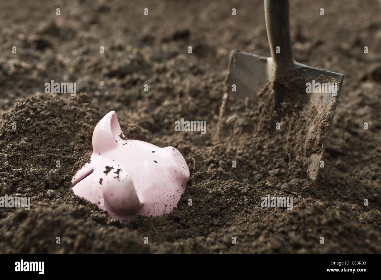 Schaufel ausgraben Sparschwein Stockbild