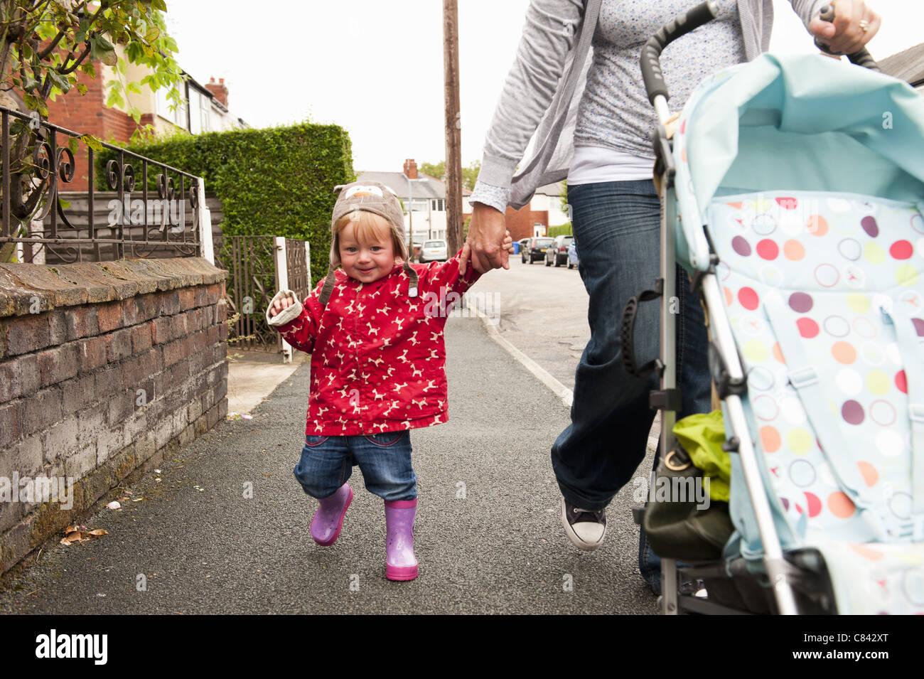 Kleinkind Mädchen gehen mit Mutter Stockbild