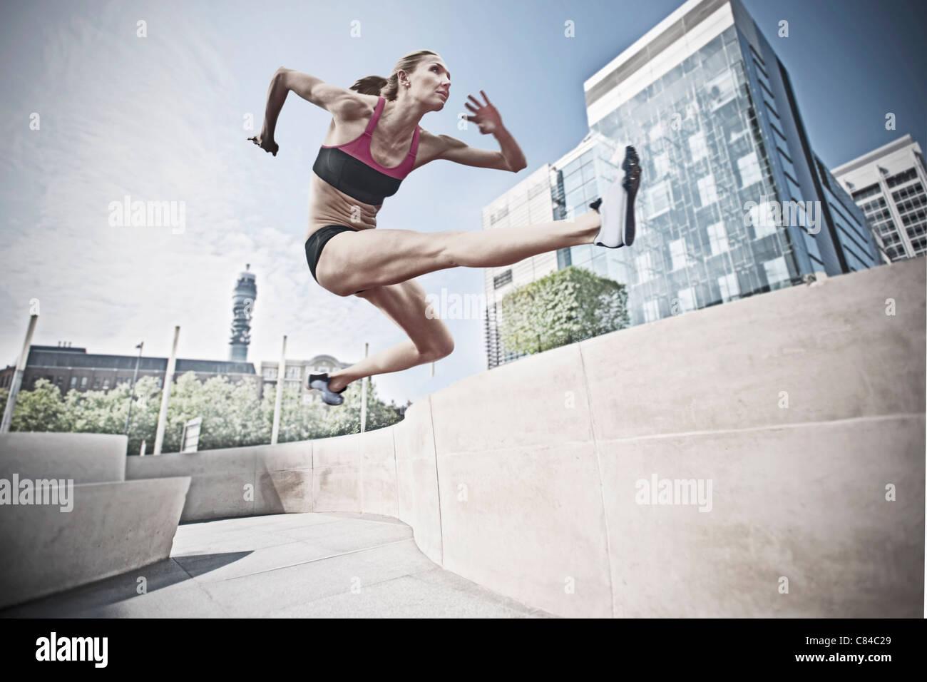 Athleten springen über Skulptur im öffentlichen Raum Stockbild