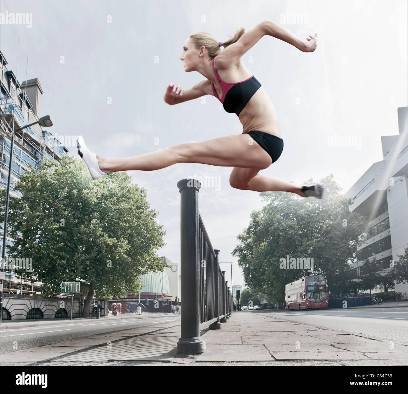 Athleten springen über Geländer auf Straße Stockfoto