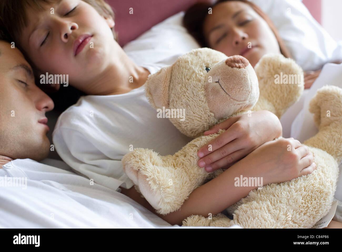 Jungen schlafen im Bett mit seinen Eltern, mit Teddy Bär Stockfoto