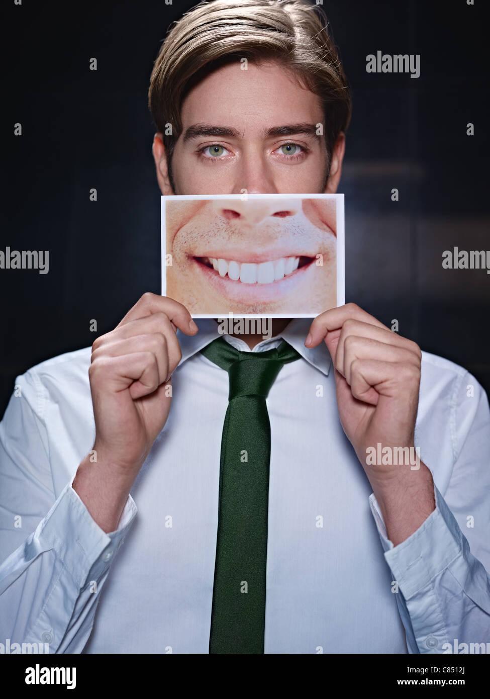 junger Geschäftsmann mit Foto von toothy Lächeln auf schwarzem Hintergrund. Vertikale Form, Vorderansicht, Stockbild