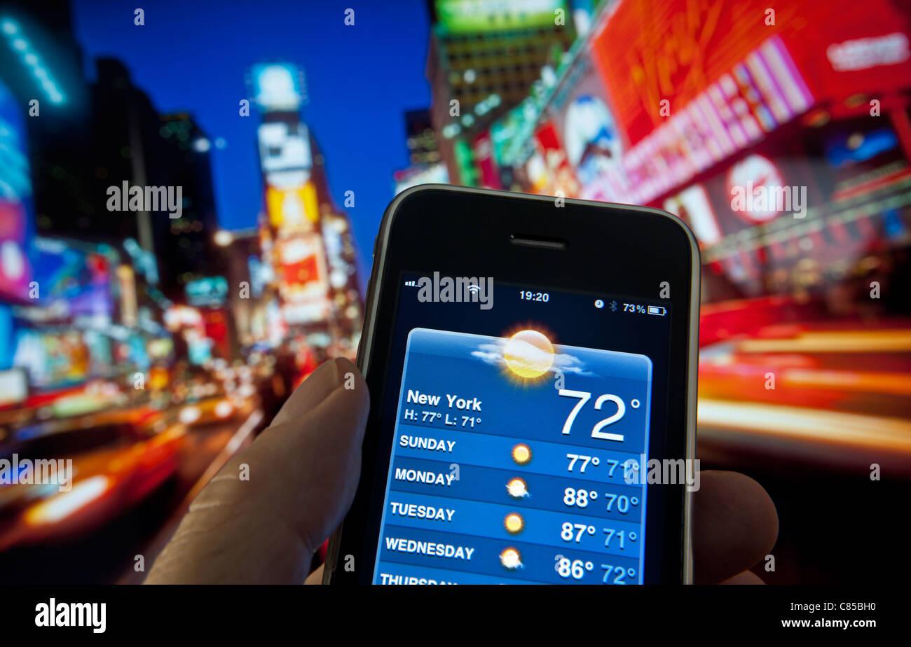 SMARTPHONE WETTER APP Times Square in der Dämmerung mit Hand, Apple iPhone, Bildschirm, der in der Woche vom Stockbild
