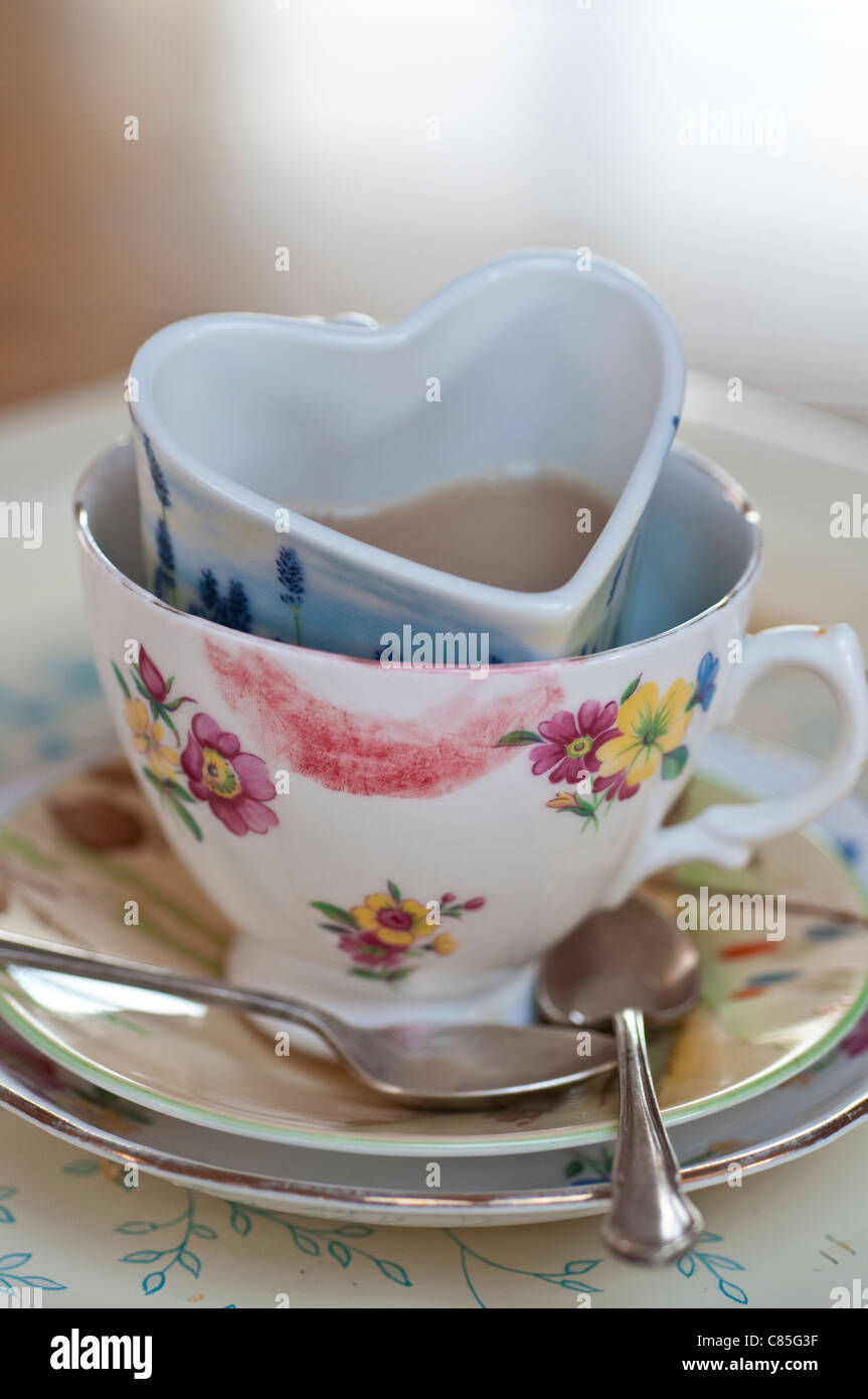 Schmutzige Tassen Tee in einander, verschmiert eines davon mit Lippenstift den anderen Herzform Stockbild