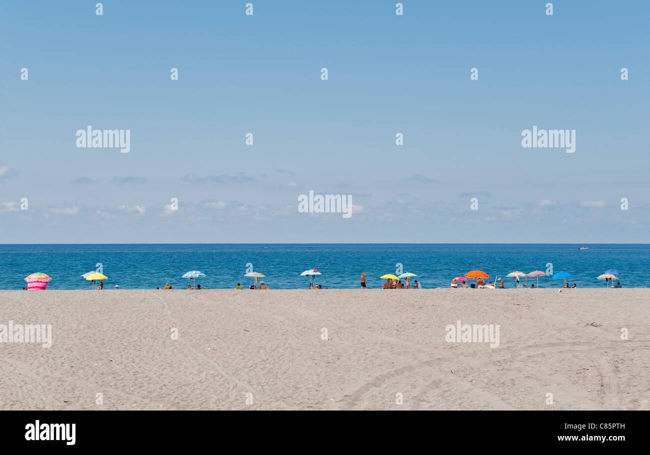 Scalea, Kalabrien, Italien. Eine Linie der Sonnenschirme gegen das blaue Tyrrhenische Meer Stockbild