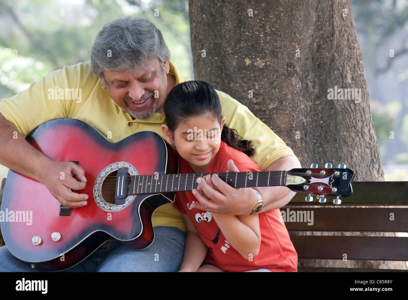Großvater lehrt seine Enkelin, Gitarre zu spielen Stockfoto