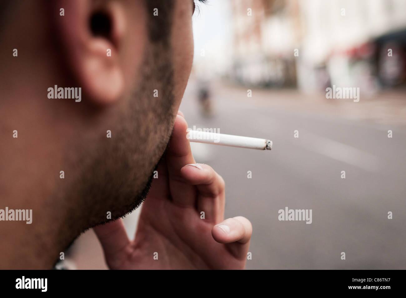 Junger Mann raucht eine Zigarette Stockbild