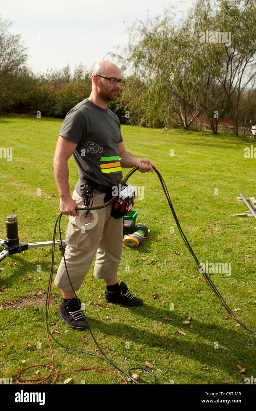 Eine Kamera Assistent Mann Kabel Basher arbeiten auf die Lage Aufzeichnung einer TV-Drama-Serie, UK Stockfoto