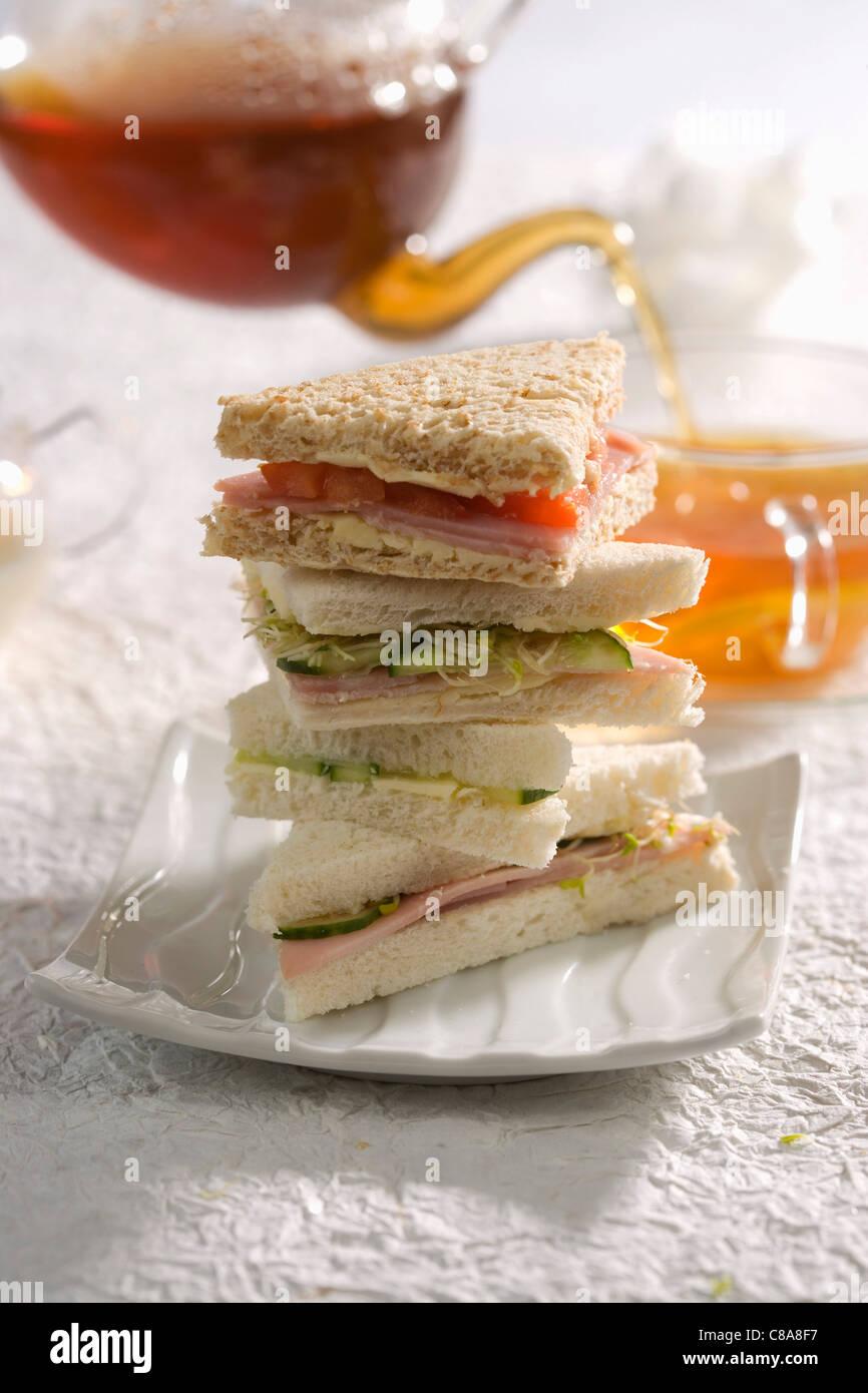 Haufen von Schinken-Club-Sandwiches und Tee mit Zitrone Stockbild