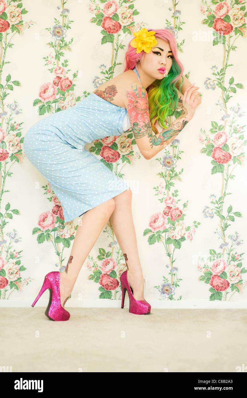 Junge Frau mit high Heels posiert auf mysteriöse Weise über Tapete Stockbild