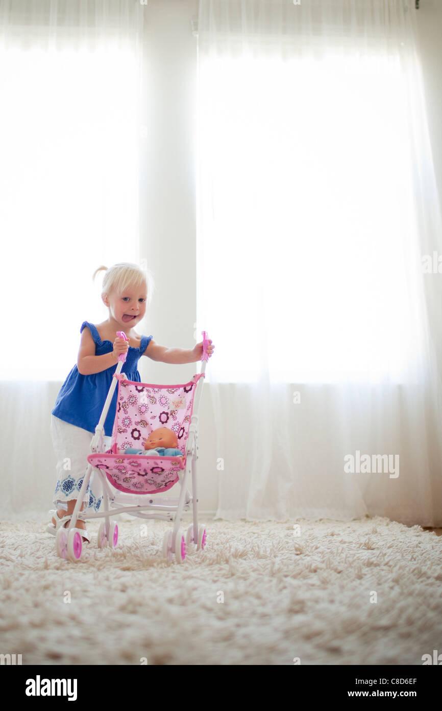 Kleinkind Mädchen schieben Spielzeug Kinderwagen mit Baby-Puppe Stockfoto